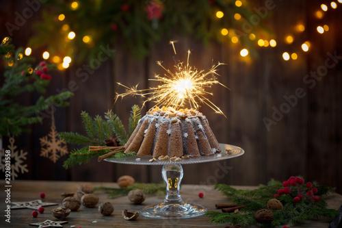 Fotografía  Christmas cake ahd fir branch  on dark wooden background