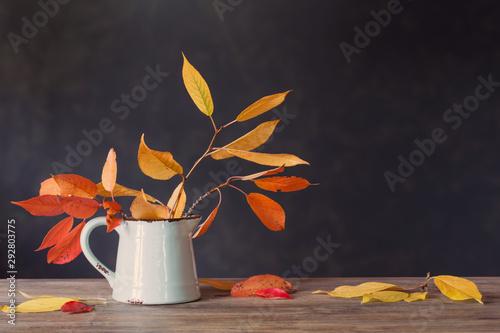 Fotografía  autumn leaves in jug on wooden table on dark background