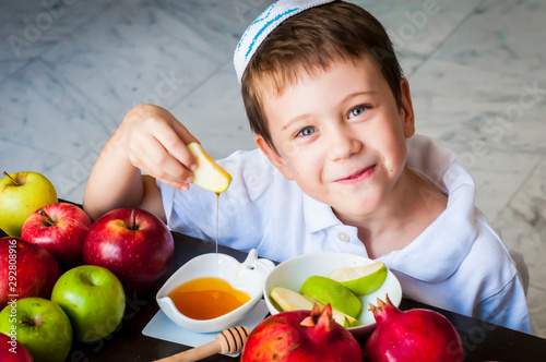 Fotografie, Tablou Cute adorable Caucasian Jewish child dipping an apple piece into honey on the Jewish New Year holiday of Rosh Hashanah concept image