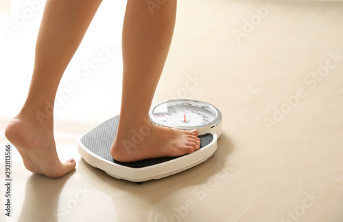 Fotografie, Obraz  Woman stepping on floor scales indoors, space for text