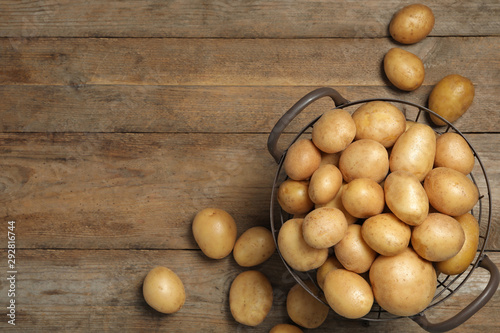 Raw fresh organic potatoes on wooden background, top view. Space for text