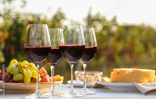 Fototapeta Red wine and snacks served for picnic on white wooden table outdoors obraz