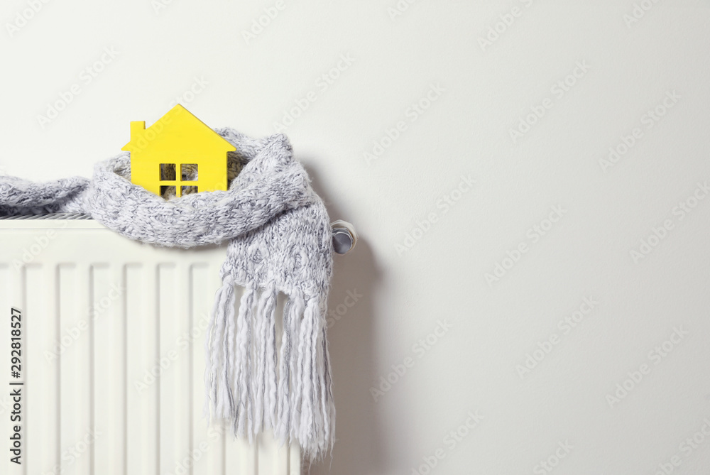 Fototapeta House model wrapped in scarf on radiator indoors, space for text. Winter heating efficiency