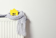 canvas print picture - House model wrapped in scarf on radiator indoors, space for text. Winter heating efficiency
