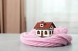 Leinwandbild Motiv Wooden house model and scarf on grey table indoors. Heating efficiency