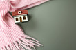 Leinwandbild Motiv Wooden house model and pink scarf on  grey background, top view with space for text. Heating efficiency
