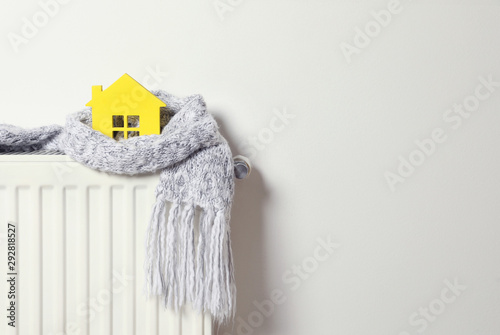 Obraz House model wrapped in scarf on radiator indoors, space for text. Winter heating efficiency - fototapety do salonu