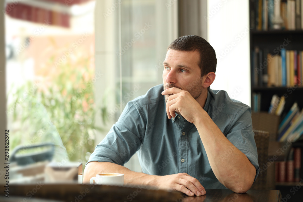 Fototapeta Pensive man in a coffee shop looking through a window
