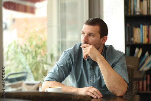 Fotomural  Pensive man in a coffee shop looking through a window
