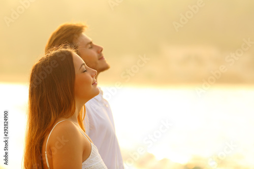 Relaxed couple on the beach breathing fresh air at sunset - 292824900
