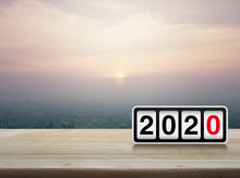 Retro Flip Clock With 2020 Text On Wooden Table Over Modern City Tower And Skyscraper At Sunset, Vintage Style, Happy New Year 2020 Cover Concept