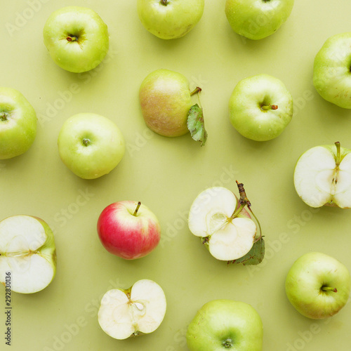 Red apple among green ones on green background flat layout top view. Fruits pattern.  - 292830136