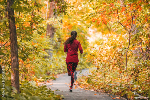 Leinwand Poster  Run woman jogging in outdoor fall autumn foliage nature background in forest