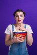 canvas print picture - Pretty lady holding popcorn container watching horror movie wear casual outfit isolated at purple background