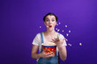 canvas print picture - Portrait of girl throwing popcorn on blue background