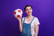 canvas print picture - Portrait of smilling girl holding a soccer ball over isolated blue wall at studio