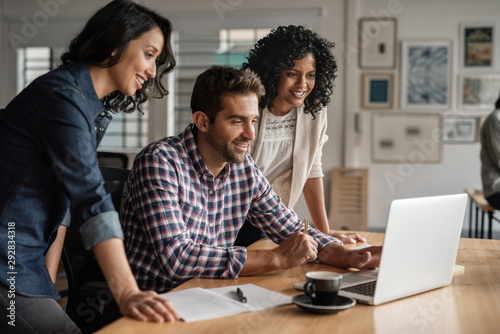 Obraz Smiling group of designers working together on an office laptop - fototapety do salonu