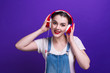 canvas print picture - Portrait of happiness girl in big red headphones isolated on blue background at studio.