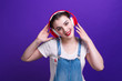 canvas print picture - Portrait of happiness woman in big red headphones isolated on blue background at studio.