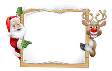 Santa Claus And Christmas Reindeer Cartoon Characters Peeking Around A Wooden Sign And Pointing At It