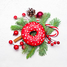 Christmas Card Composition With Donut, Green Fir Twig, Cone, Baubles And Red Holly Berries On White Stucco Plaster Texture. Xmas Card, Top View Flat Lay