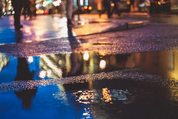 Night street in a big city after rain, night lights, bokeh, blur and reflection in a puddle