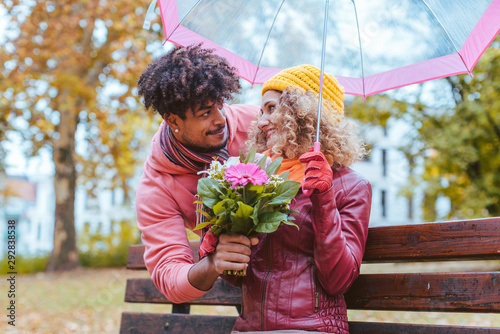 Fotografia, Obraz Man surprising his wife with a bouquet of flowers on a drizzly fall day