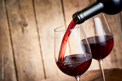 Rich red cabernet wine pouring into a glass Canvas Print