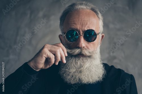 Obraz Close up photo of attractive harsh masculine pensioner in eyewear eyeglasses touching his moustache isolated over grey background - fototapety do salonu