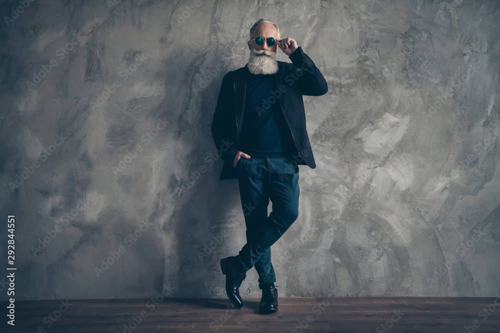 Fototapeta Full size photo of attractive harsh masculine man with eyewear eyeglasses standing near wall looking wearing coat jacket trousers shoes isolated over grey background