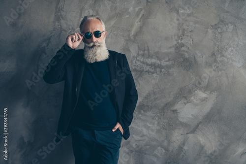 Fotografia  Portrait intelligent harsh masculine gentleman touching his specs looking wearin