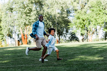 Happy African American Father And Son Running On Grass