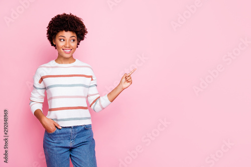 Obraz Photo of pretty dark skin wavy lady indicating finger to empty space showing good prices banner wear striped jumper isolated pastel pink color background - fototapety do salonu
