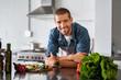 Leinwandbild Motiv Happy man ready to cook in kitchen
