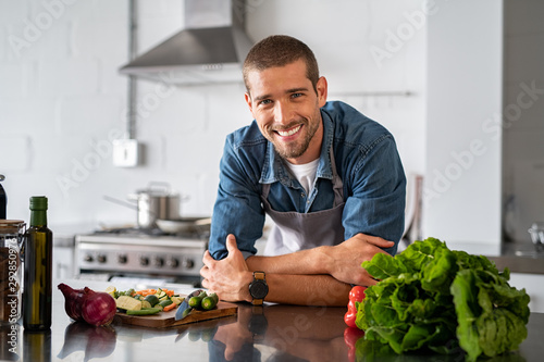 Happy man ready to cook in kitchen Canvas