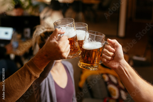 Photo Group of happy friends drinking and toasting beer at bar