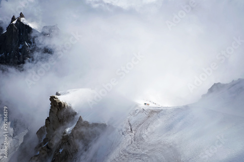 Snowy Amountsin peaks in alps with small unrecognizable figures of alpinists Canvas Print
