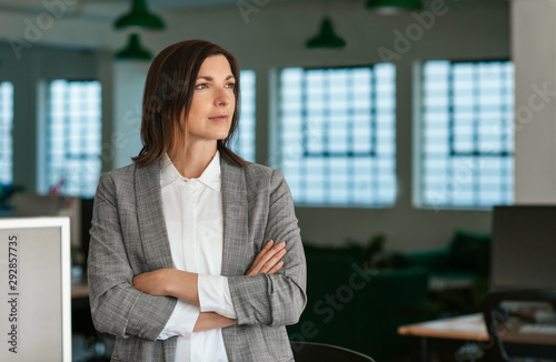 Photo Businesswoman deep in thought while standing by her office desk