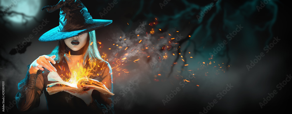 Fototapeta Halloween Witch girl with magic Book of spells portrait. Beautiful young woman in witches hat conjuring, making witchcraft. Over spooky dark magic forest background. Wide Halloween party art design.