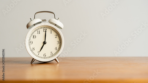 Photo White alarm clock on brown wood desk and cream wallpaper textured background wit
