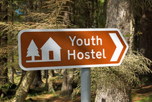 Youth Hostel Sign In UK, With Blurred Forest Background Taken On Sunny Day At Rowardennan On West Highland Way