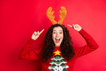 Portrait Of Shocked Crazy Cheerful Student Girl Point Index Finger Her Yellow Reindeer Headband Enjoy X-mas Masquerade Party Wear Stylish Sweater With Christmas Tree Ornament Isolated Red Color