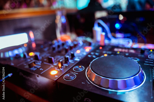 control DJ for mixing music with blurred people dancing at party in nightclub - 292862594