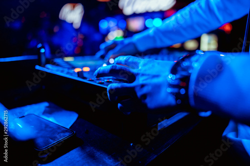 control DJ for mixing music with blurred people dancing at party in nightclub - 292862715