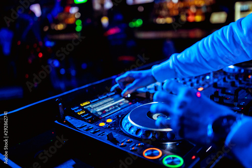 control DJ for mixing music with blurred people dancing at party in nightclub - 292862741