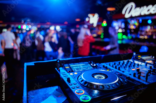 control DJ for mixing music with blurred people dancing at party in nightclub - 292862790