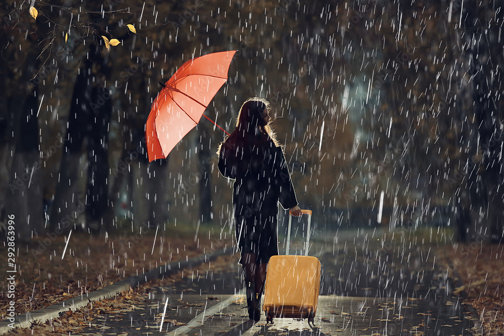 Fototapeta night the girl is walking with an umbrella and a suitcase in the autumn park, the concept of travel, sadness, parting, divorce