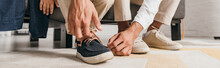 Panoramic Shot Of Father Tying Shoelaces To Son