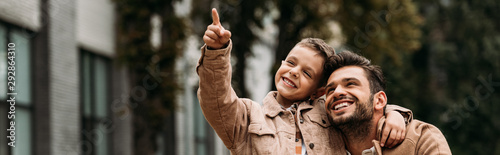Fotografía panoramic shot of smiling son and dad embracing in autumn day on street
