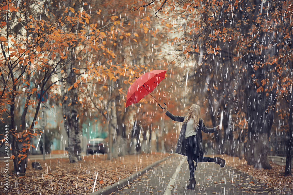 Fototapeta October walk in the rain, a young woman with a red umbrella in the autumn city park, autumn look